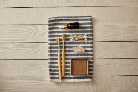 Foto de Endecha plana de diversos artículos de cuidado e higiene dispuestas en toalla de rayas en la superficie de madera blanca, cero residuos concepto - Imagen libre de derechos