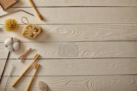 Foto de Vista superior de diversos artículos de higiene y cuidado en la superficie de madera blanca, cero concepto de residuos - Imagen libre de derechos