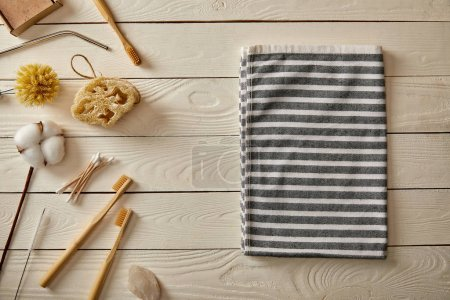 Photo for Top view of different hygiene and care items and striped towel on white wooden surface, zero waste concept - Royalty Free Image