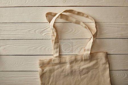 Photo pour Vue du dessus du sac de coton vide sur une surface en bois blanc, concept zéro déchet - image libre de droit