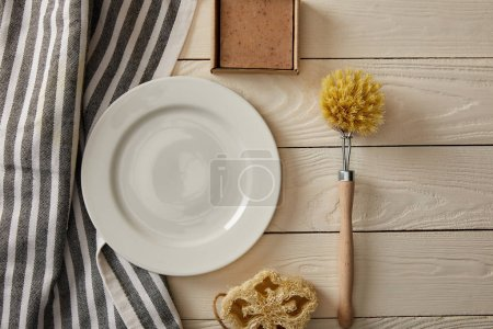Photo for Top view of empty white plate, striped towel and different cleaning items on white wooden surface, zero waste concept - Royalty Free Image