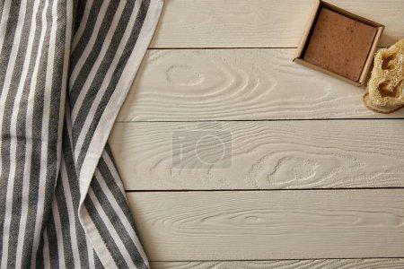 Photo pour Vue de dessus des objets de soins et hygiène et serviette rayée sur une surface en bois blanche, zéro déchets concept - image libre de droit