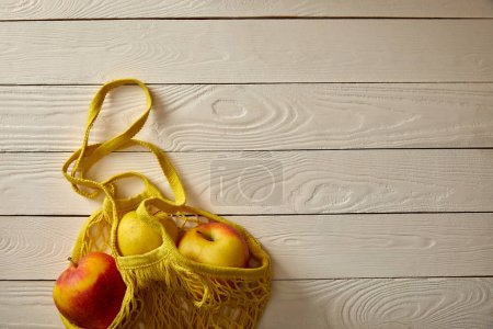 Photo for Top view of string bag with rape apples on white wooden surface, zero waste concept - Royalty Free Image