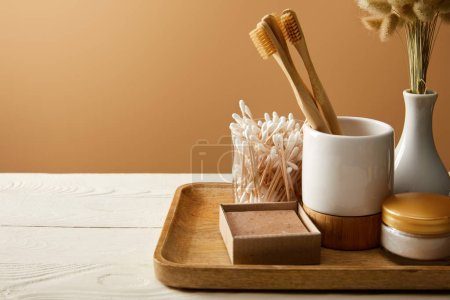 Photo pour Wooden tray with different hygiene and care items and vase of spikelets on white wooden surface, zero waste concept - image libre de droit