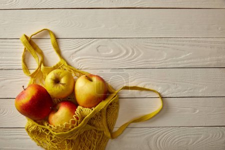 Photo for Top view of string bag full of rape apples on white wooden surface, zero waste concept - Royalty Free Image