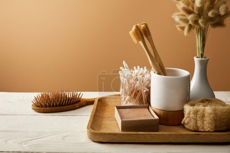 Photo for Wooden tray with different hygiene and care items, and hair brush on white wooden surface, zero waste concept - Royalty Free Image