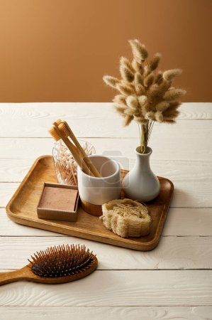 Photo for Hair brush, wooden tray with vase of spikelets and various hygiene and care items on white wooden surface, zero waste concept - Royalty Free Image