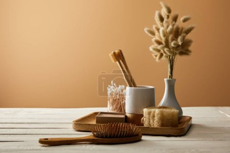 Photo for Wooden tray with different hygiene and care items, vase of spikelets, and hair brush on white wooden surface, zero waste concept - Royalty Free Image