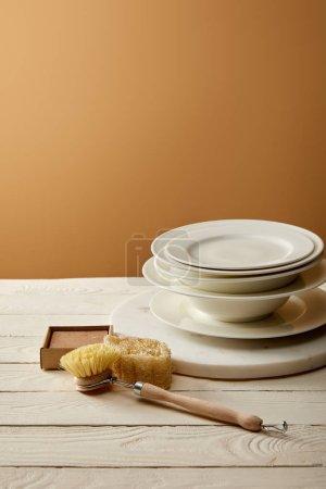 Photo pour Pile de plaques et divers articles de nettoyage sur la surface en bois blanc, concept zéro déchet - image libre de droit
