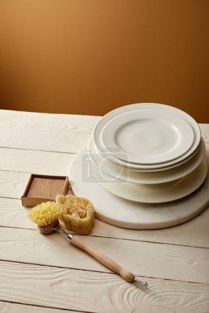 Photo pour Plaques empilées et divers articles de nettoyage sur la surface en bois blanc, concept zéro déchet - image libre de droit