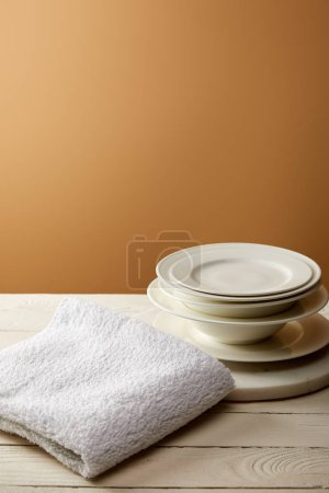 Photo for Stack of plates and terry cotton towel on white wooden surface - Royalty Free Image