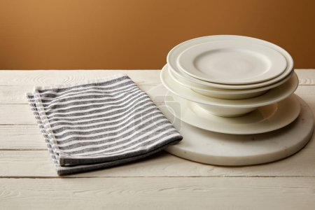 Photo for Stack of white plates and striped cotton towel on white wooden surface - Royalty Free Image