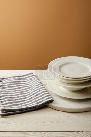 Photo for Striped cotton towel and stack of plates on white wooden surface - Royalty Free Image