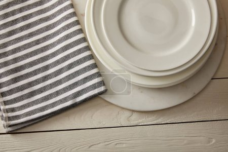 Photo for Top view of stacked plates and striped cotton towel on white wooden surface - Royalty Free Image