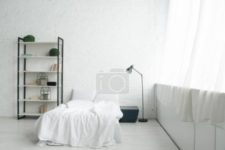 Photo for Interior of cozy bedroom with pillows on bed, nightstand, lamp and rack - Royalty Free Image
