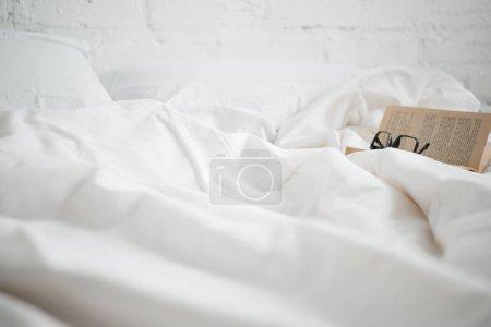 Photo pour Focus sélectif du livre avec des lunettes sur lit blanc - image libre de droit