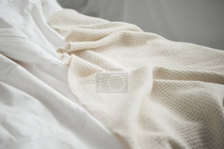 Photo for Close up of cozy empty bed with white blanket and sheets - Royalty Free Image