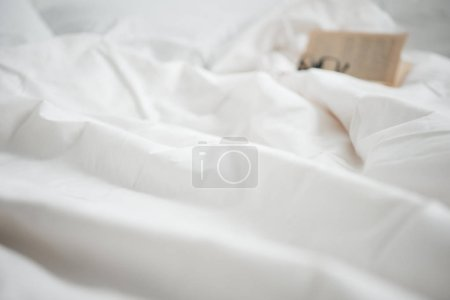 Photo for Selective focus of book and glasses on white empty bed - Royalty Free Image