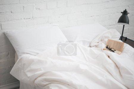 Photo pour Verres et livre sur le lit avec couverture blanche et oreillers, lampe - image libre de droit