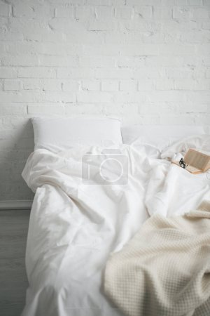 Photo pour Verres et réserver au lit avec couverture blanche et oreillers - image libre de droit