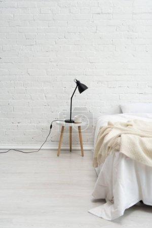 Innenraum des gemütlichen Schlafzimmers mit Kissen auf dem Bett, Lampe und Kaffeetasse auf Hocker