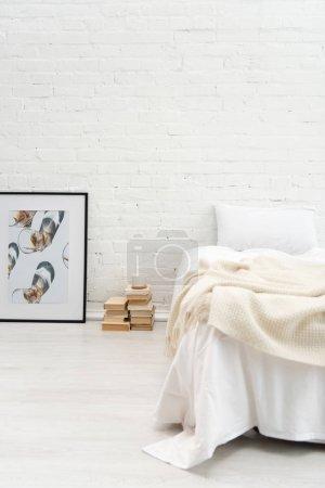 Schlafzimmer mit Kopfkissen auf leerem Bett und Büchern, Bild auf dem Boden