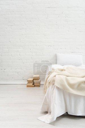 Schlafzimmer mit weißem Kissen auf leerem Bett und Büchern auf dem Boden