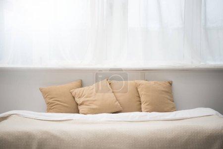 Foto de Acogedora cama con almohadas marrones y blanco manto - Imagen libre de derechos
