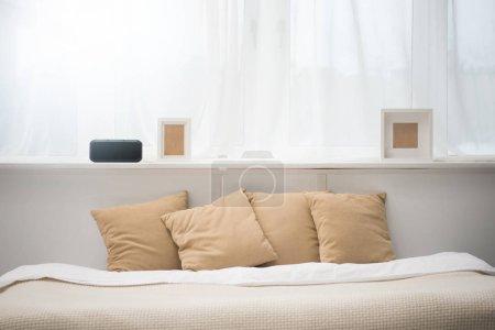 Photo pour Chambre avec oreillers marron sur le lit, réveil et cadres photo - image libre de droit