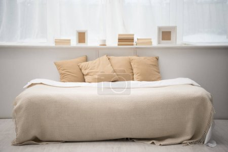 Photo for Interior of bedroom with brown pillows on bed, books, coffee cup and photo frames - Royalty Free Image