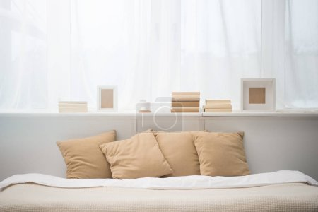 Photo pour Chambre avec oreillers marron sur le lit, livres, tasse à café et cadres photo - image libre de droit