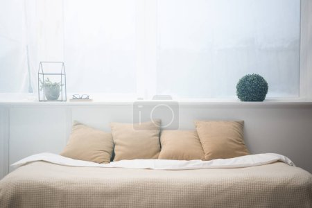 Photo for Bedroom with brown pillows and white blanket on empty bed, plants and glasses - Royalty Free Image
