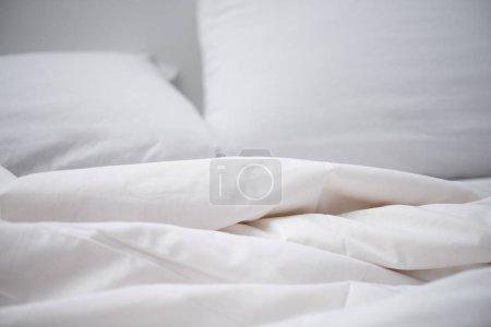 Photo pour Concentration sélective du lit vide avec couverture blanche et oreiller - image libre de droit