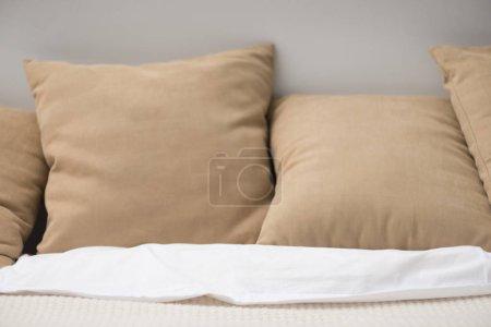 Photo pour Gros plan des oreillers bruns sur le lit vide confortable - image libre de droit
