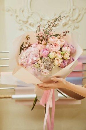 Photo pour Vue recadrée du fleuriste tenant un bouquet de roses et de pivoines à l'espace de travail - image libre de droit
