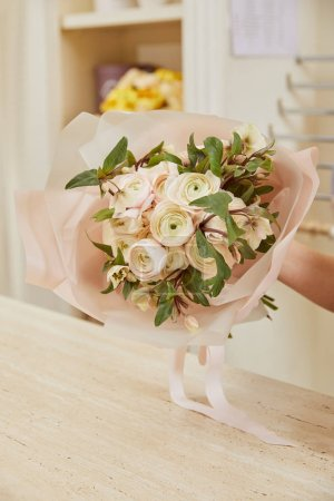 Photo for Partial view of florist holding bouquet of white peonies at workplace - Royalty Free Image