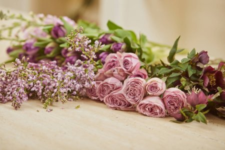 Photo for Purple tulips, peonies and lilac on table at flower shop - Royalty Free Image
