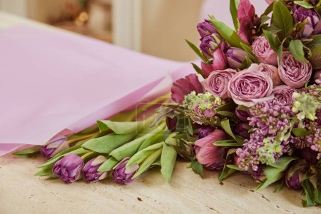 Photo for Selective focus of purple tulips, peonies and lilac on table - Royalty Free Image