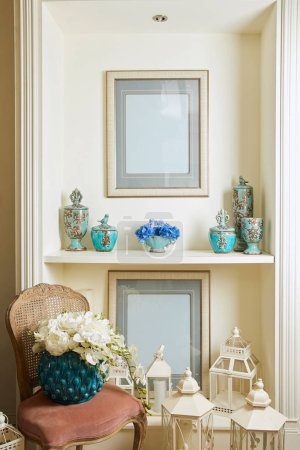 Photo for Interior of room with chair, picture frames, bouquets and set on shelf - Royalty Free Image