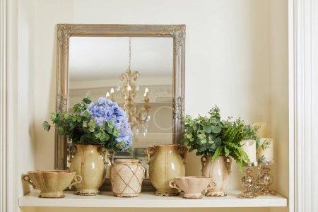 Photo pour Mirror, beige set with and flowers on shelf - image libre de droit