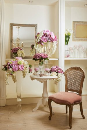 Photo pour Interior of room with chair, mirror, bouquets in glass vases - image libre de droit