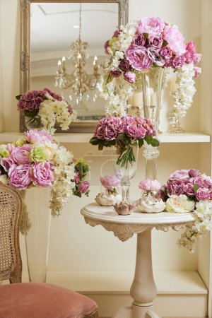 Photo pour Interior of room with chair, mirror, flowers in glass vases - image libre de droit