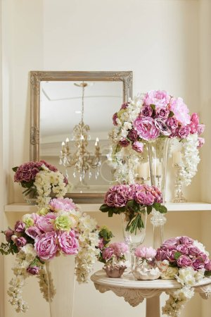 Photo pour Mirror, white and purple flowers in glass vases on table and shelf - image libre de droit