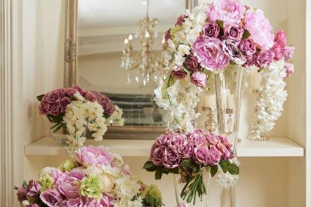 Photo pour Mirror, white and purple flowers in glass vases - image libre de droit