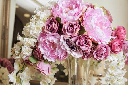 Photo pour Close up of white and purple flowers in glass vase - image libre de droit
