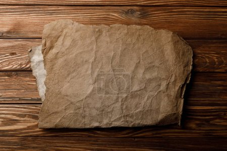 Photo for Brown aged parchment sheet lying on wooden background - Royalty Free Image