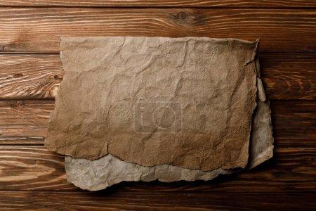 Photo pour Vieille feuille de parchemin marron couchée sur fond en bois - image libre de droit