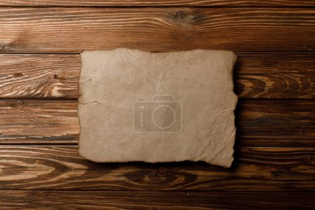 brown old parchment paper lying on wooden background