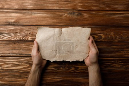 Photo for Cropped view of man holding aged paper sheet in hands - Royalty Free Image