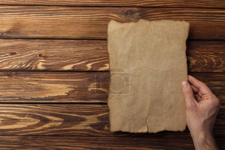 Photo for Top view of brown parchment paper lying on wooden background - Royalty Free Image